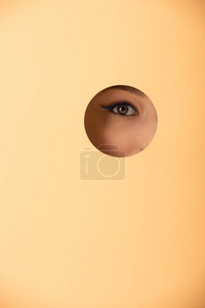 Photo for Cropped view of woman looking at camera through hole on pastel orange - Royalty Free Image