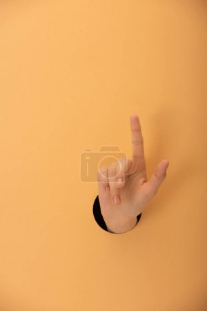 cropped view of hole with hand of woman pointing with finger on orange
