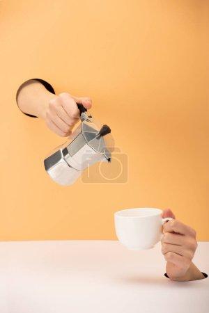 Photo pour Vue recadrée de la femme tenant la cafetière avec tasse sur orange et blanc - image libre de droit