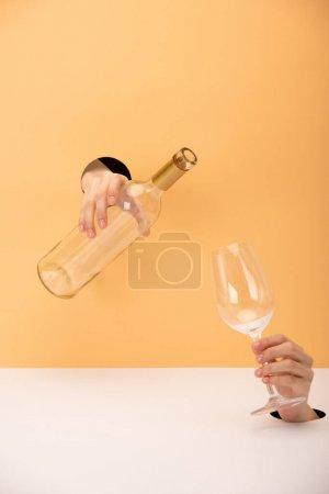 Photo pour Vue recadrée de la femme tenant bouteille et verre sur orange et blanc - image libre de droit