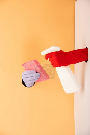 Photo pour Vue recadrée des mains dans des gants tenant le flacon pulvérisateur et l'éponge sur blanc et orange - image libre de droit