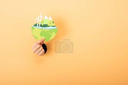 Photo pour Vue recadrée du papier à main coupé avec planète sur orange - image libre de droit