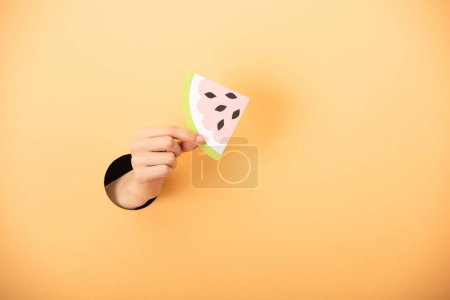 cropped view of woman holding paper watermelon on orange