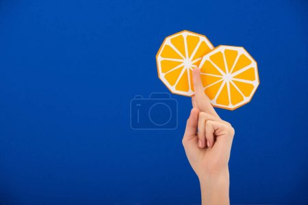 Photo for Cropped view of woman holding paper cut orange isolated on blue - Royalty Free Image