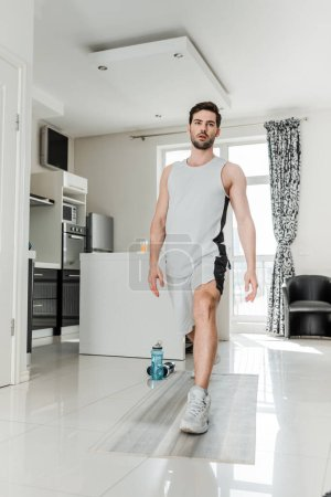 Handsome man working out on fitness mat near sports bottle and barbells at home