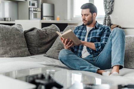 Photo pour Focus sélectif du bel homme lisant le livre sur le canapé à la maison - image libre de droit