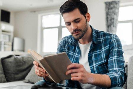 Photo pour Focus sélectif de bel homme en chemise tressée livre de lecture à la maison - image libre de droit