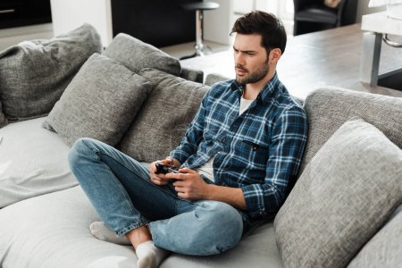 KYIV, UKRAINE - APRIL 13, 2020: Handsome man holding joystick while playing video game on sofa at home