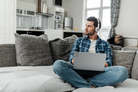 Photo for Handsome freelancer in headphones using laptop on sofa at home - Royalty Free Image