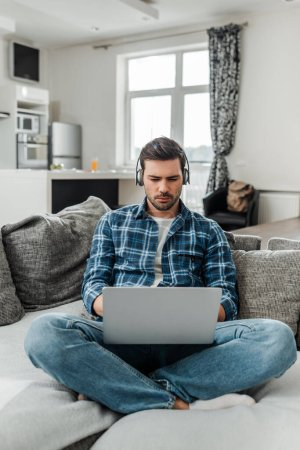 Freelancer listening music in headphones and using laptop on couch at home
