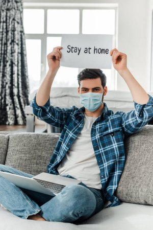 Photo for Freelancer in medial mask holding card with stay at home lettering near laptop on couch - Royalty Free Image