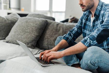Photo pour Vue recadrée de pigiste travaillant sur ordinateur portable à la maison - image libre de droit