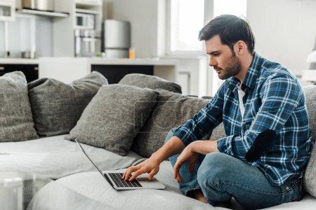 Photo pour Vue latérale du bel homme utilisant un ordinateur portable sur le canapé à la maison - image libre de droit