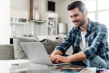 Photo for Selective focus of smiling freelancer using laptop on coffee table near magazines and smartphone - Royalty Free Image