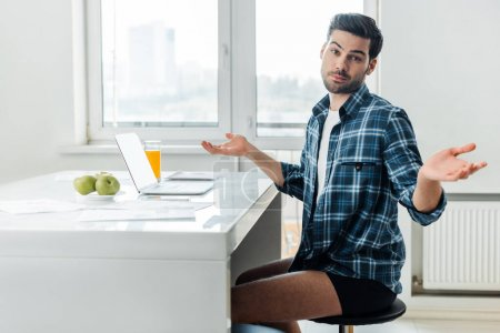 Photo for Side view of freelancer in shirt and panties showing confused sign at camera near laptop and papers on table - Royalty Free Image