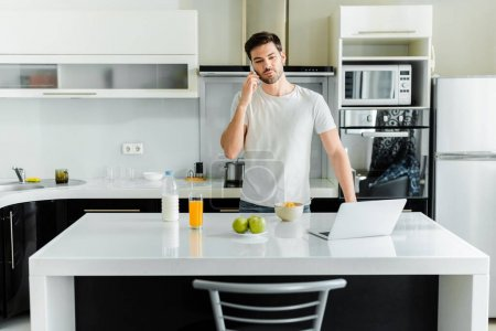 Man talking on smartphone near laptop, cereals and orange juice on kitchen table