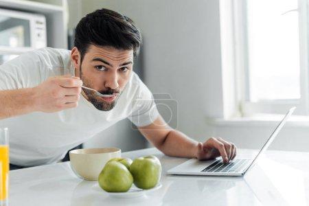 Selektiver Fokus des Mannes, der beim Frühstück in die Kamera schaut und Laptop in der Küche benutzt