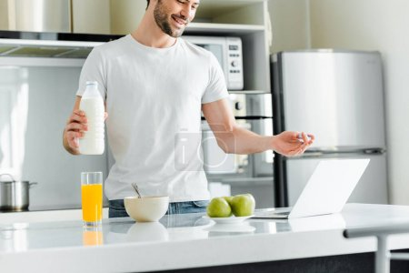Selective focus of smiling man holding bottle of milk while having video call on laptop on kitchen table