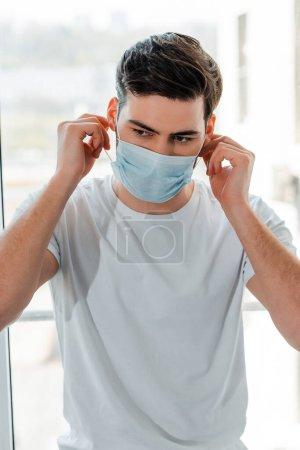 Photo pour Homme ajustant masque médical près de la fenêtre à la maison - image libre de droit