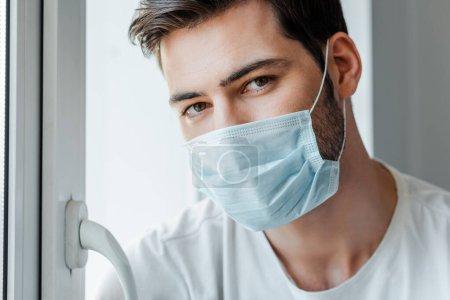 Photo pour Homme en masque médical regardant la caméra près de la fenêtre à la maison - image libre de droit