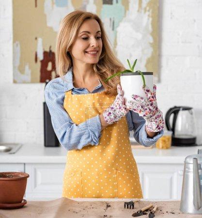 Photo pour Femme regardant pot de fleurs avec aloès et souriant près de la table avec des outils de jardinage dans la cuisine - image libre de droit