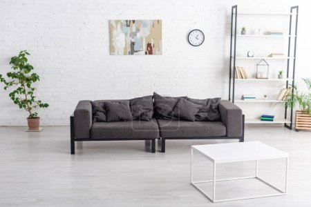 Grey sofa near coffee table, flowerpots with houseplants, rack and clock with picture on wall in living room