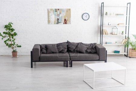 Photo pour Canapé gris près de la table basse, pots de fleurs avec plantes d'intérieur, rack et horloge avec photo sur le mur dans le salon - image libre de droit