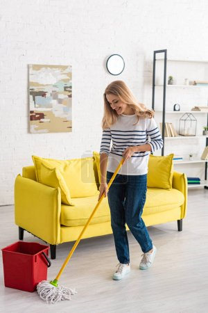 Beautiful woman cleaning up with mop and smiling in living room