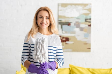 Photo for Front view of blonde woman in rubber gloves smiling, looking at camera and holding mop in living room - Royalty Free Image