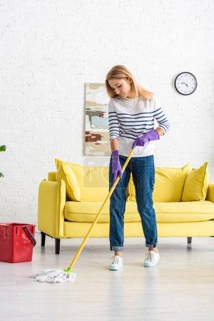 Photo pour Femme en gants de caoutchouc sol de nettoyage près du seau dans le salon - image libre de droit