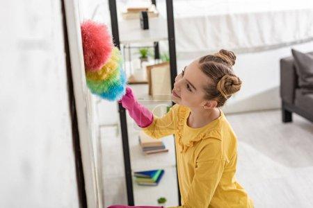 Vista de ángulo alto del niño lindo sonriendo y limpiando con plumero en la sala de estar
