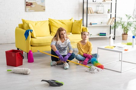 Photo for Tired mother and daughter with crossed legs and cleaning supplies on floor near coffee table in living room - Royalty Free Image