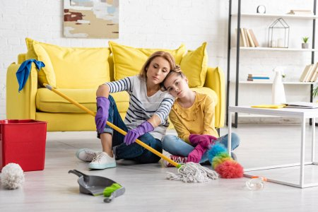 Photo for Tired mother and daughter with crossed legs and cleaning supplies leaning to each other on floor near coffee table in living room - Royalty Free Image