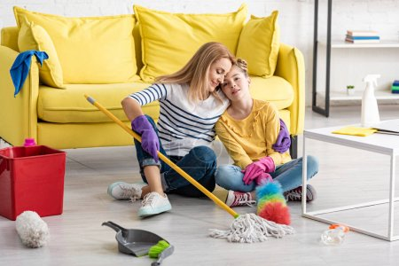 Tired mother hugging daughter with cleaning supplies on floor near coffee table in living room