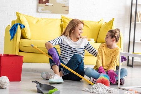 Photo pour Mère et fille étonnées avec les jambes croisées et les fournitures de nettoyage se regardant sur le sol dans le salon - image libre de droit