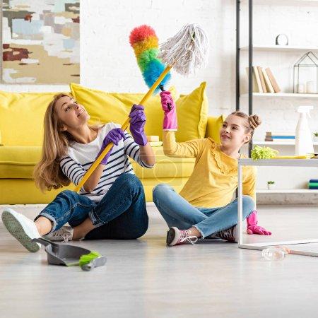 Photo pour Mère et fille se battant avec la vadrouille et plumeau et souriant près de la table basse et brosse à poussière sur le sol dans le salon - image libre de droit