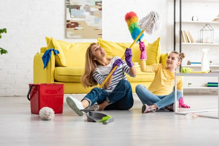 Photo for Mother and daughter fighting with mop and feather duster near coffee table and cleaning supplies on floor in living room - Royalty Free Image