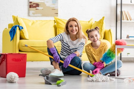 Photo for Mother and cute daughter with cleaning supplies smiling and looking at camera on floor in living room - Royalty Free Image