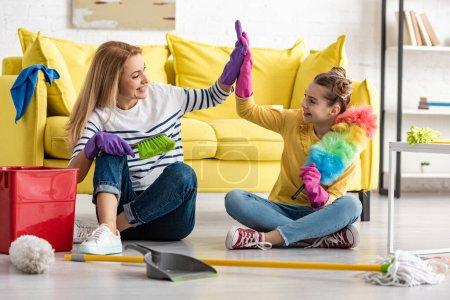 Foto de Madre y linda hija con los suministros de limpieza que dan los cinco primeros, sonriendo y mirándose unos a otros en el piso en el salón. - Imagen libre de derechos