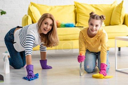 Photo pour Mère à quatre pattes et fille avec vaporisateurs et chiffons essuyant le sol, souriant et regardant la caméra dans le salon - image libre de droit
