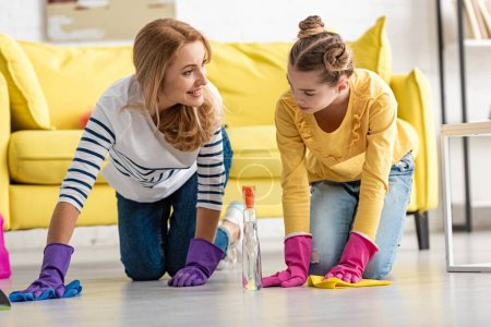 Mother and daughter on all fours wiping floor with rags in living room