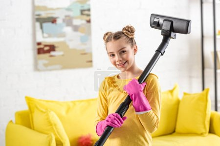 Photo for Cute child with vacuum cleaner smiling and looking at camera in living room - Royalty Free Image