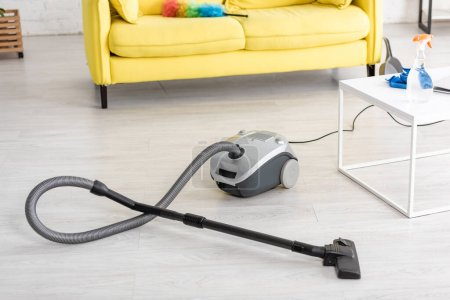 Photo for Vacuum cleaner near coffee table and sofa with feather duster in living room - Royalty Free Image