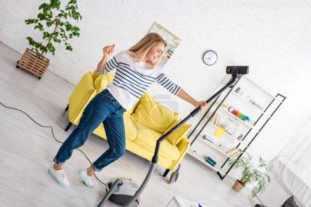 Photo pour Femme heureuse avec main tendue tenant aspirateur dans le salon - image libre de droit