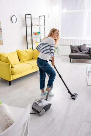 Photo for Attractive woman smiling and cleaning up with vacuum cleaner in living room - Royalty Free Image
