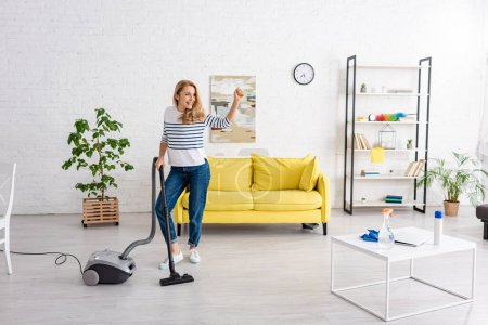 Woman with raised hand and vacuum cleaner looking away and smiling in living room