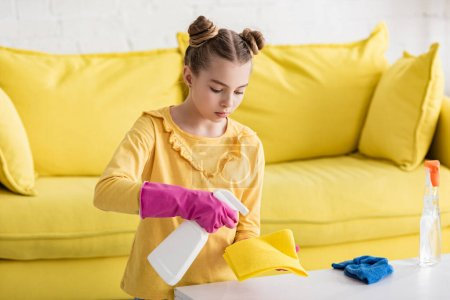 Photo for Cute child with spray bottle applying detergent on rag near coffee table and sofa in living room - Royalty Free Image