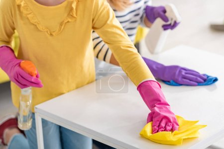 Photo for Cropped view of mother and daughter with spray bottles wiping coffee table with rags in living room - Royalty Free Image