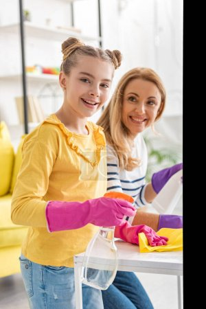 Cute child holding rag and spray bottle, smiling and looking at camera with mother near coffee table in living room