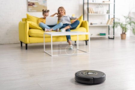 Photo for Selective focus of mother and daughter with laptop on sofa near coffee table and robotic vacuum cleaner on floor in living room - Royalty Free Image